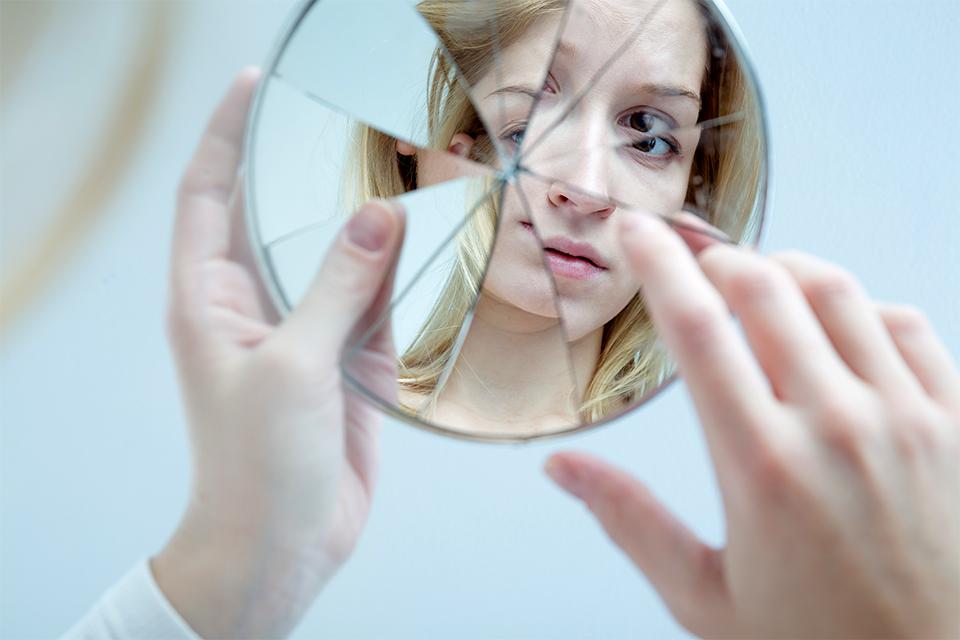 Девушка держит разбитое зеркало